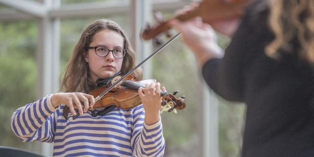 Girl in striped shirt playing violin