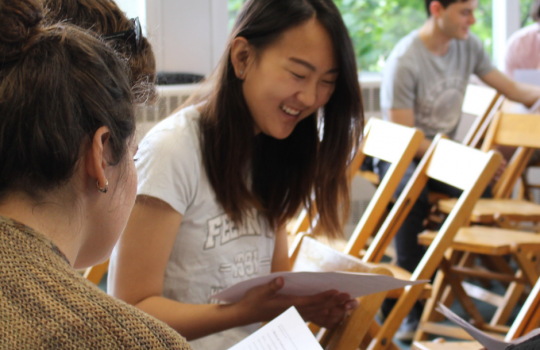 Students sitting and reviewing papers, image focuses on an Asian woman in a light gray t-shirt.