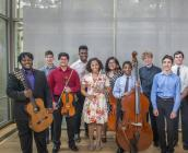 Posed photo of 11 middle- and high-school students, all standing with their instruments in front of a gray window shade. There are three female and eight make students, between them identifying as Black, Latinx and White.