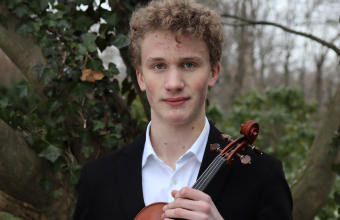 Henry Rogers, young white man with light brown curly hair, holding his violin.